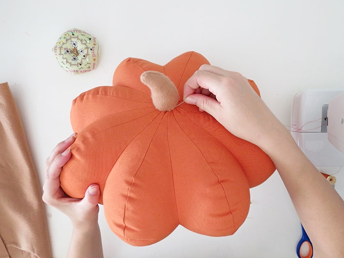 sew the stem on the pumpkin shaped pillow