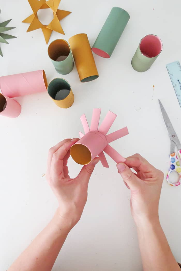 fold straps to make christmas ornament with toilet roll